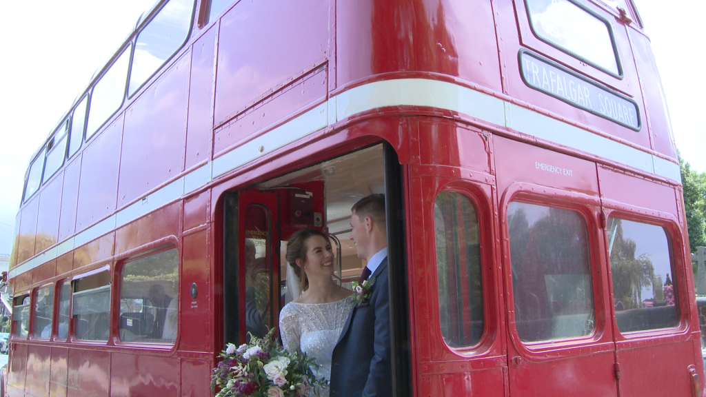 a bride and groom laugh with the photographer and videographer stood on the back of their vintage red london bus for their wedding photos in Woolton, Liverpool