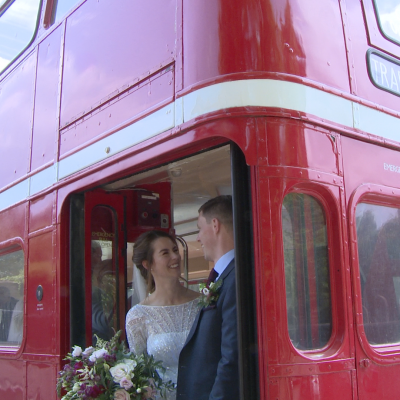 a bride and groom laugh with the photographer and videographer stood on the back of their vintage red london bus for photos in liverpool