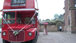 two bridesmaids hide under a red umbrella as they try to walk from the vintage london bus to the front door at Inglewood manor