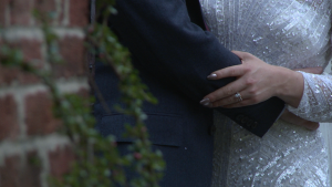 a close up of the brides wedding ring on her hand as she holds her grooms arms