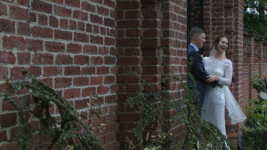 the bride and groom laugh with the wedding photographer as she takes photos by the garden gate in Inglewood manor