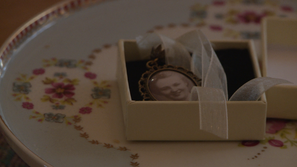 an old black and white photo of the brides nan is in a silver locket ready to hang on the brides wedding bouquet