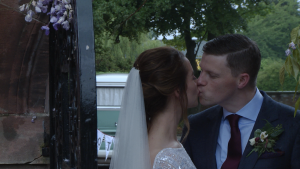 a bride and groom kiss under an archway for the photo and video at their wedding at Inglewood manor in Cheshire