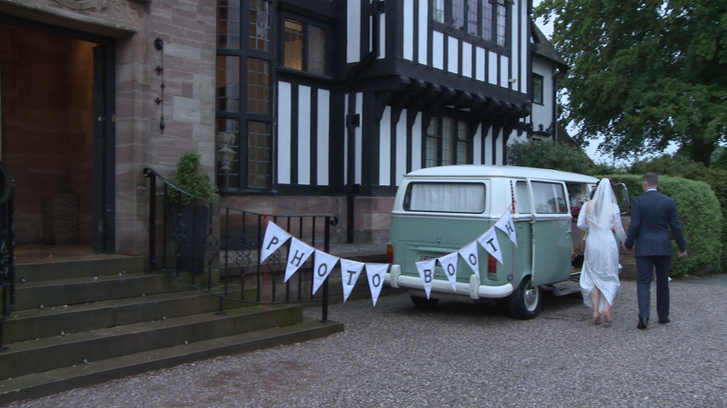 dusty the campervan photbooth is parked up as the bride and groom walk over outside inglewood manor