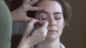 Caitlin Helsby the make up artist applies a pink eye shadow to the brides eyelid