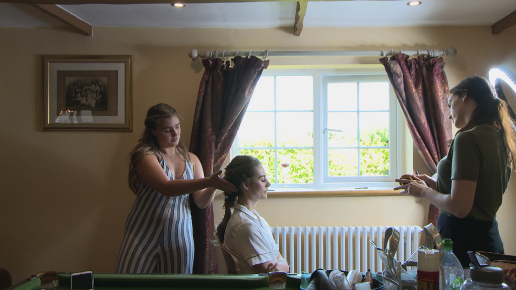 a wide shot shows the bride sitting in front of her traditional rustic cottage living room window on her wedding morning as the professional bridal hair and make up team add the finishing touches before she gets ready for her wedding in Liverpool