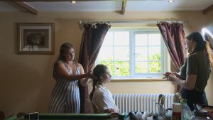 a wide shot shows the bride sitting in front of her living room window as the bridal hair and make up team add the finishing touches before she gets ready for her wedding in Liverpool