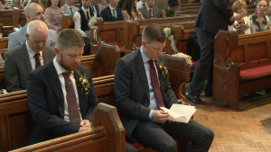 the groom and his best man sit nervously looking at their order of service with the videographer in St Peters church in Woolton
