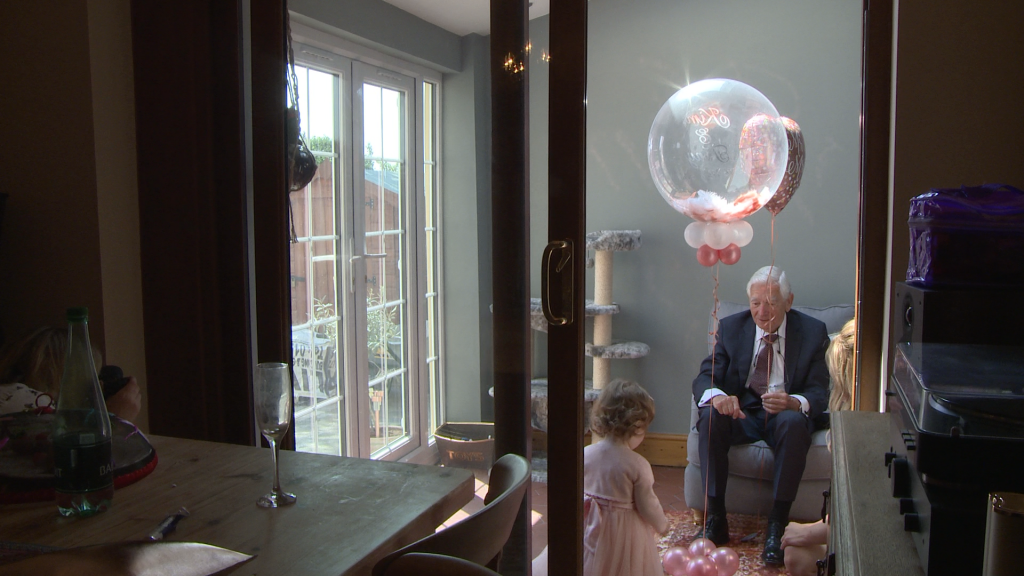 a grandad plays with balloons for a little flower girl dressed in pink