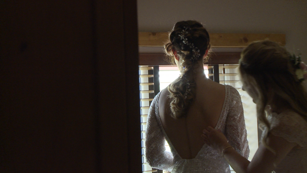 a bridesmaid does the final checks of the brides Eliza Jane Howell beaded wedding dress