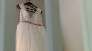 a wedding dress hangs in a bedroom with the door open from the stairs at a cottage at thornton manor
