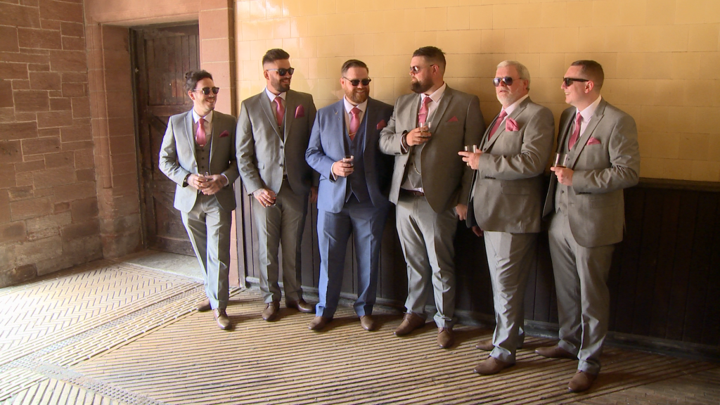 the groom and groomsman strike a cool pose for their wedding photographer in their sunglasses at thornton manor