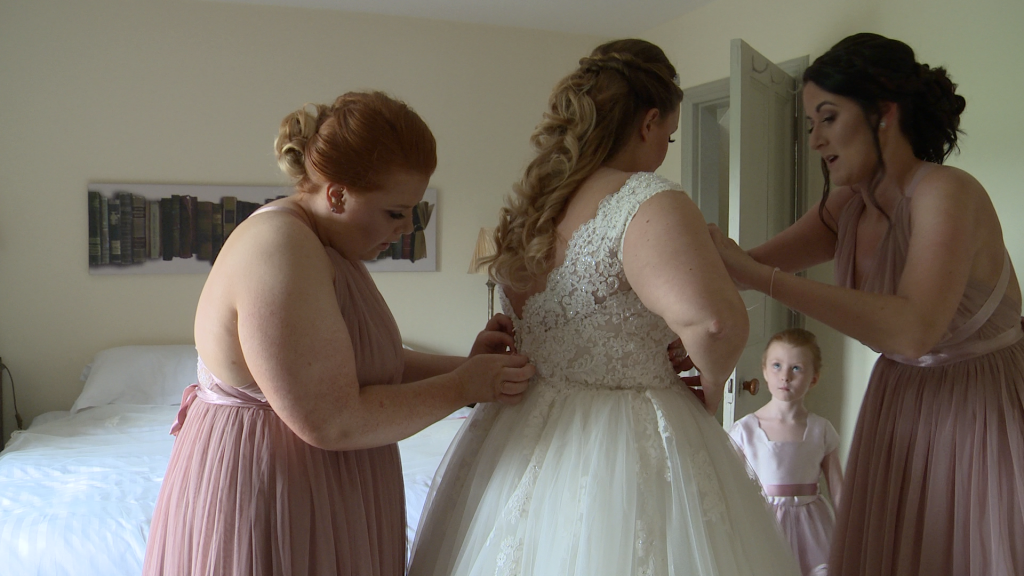 two bridesmaids help the bride fit in to her wedding dress as a flower girl looks on