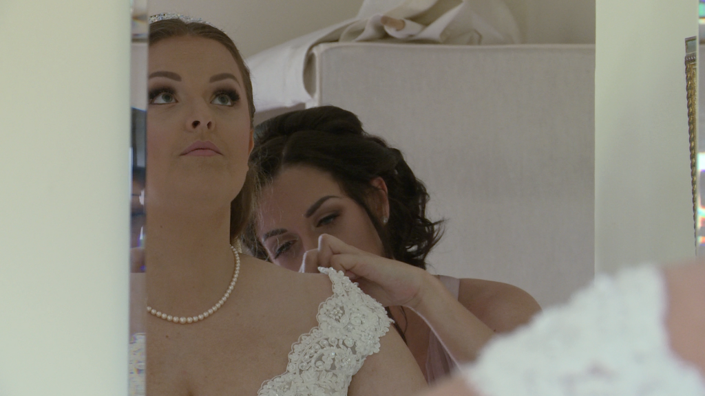 the bride looks up to compose herself as she sees herself in the mirror for the first time