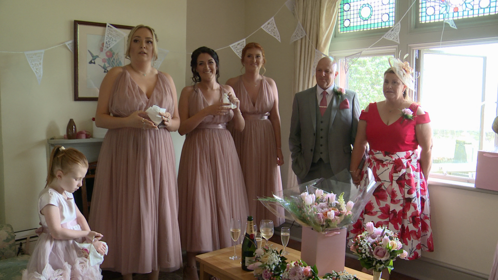 the bridesmaids , father of the bride and Mum wait eagerly for the bride to do her reveal at thornton manor