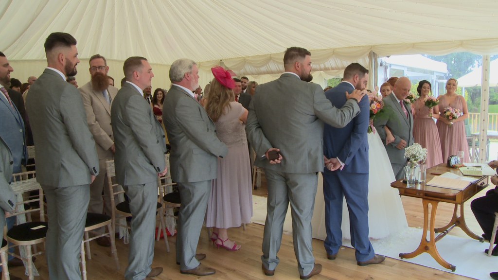 the best man reassuringly pats the groom on the shoulder as his bride arrives at the top of the aisle at the lakeside marquee