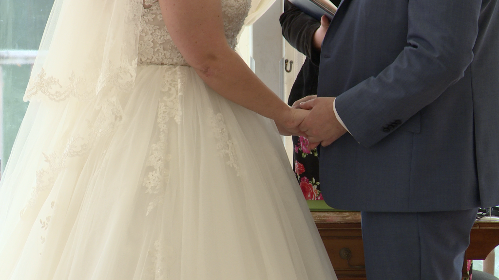 a close up of the bride and groom holding hands during the ceremony