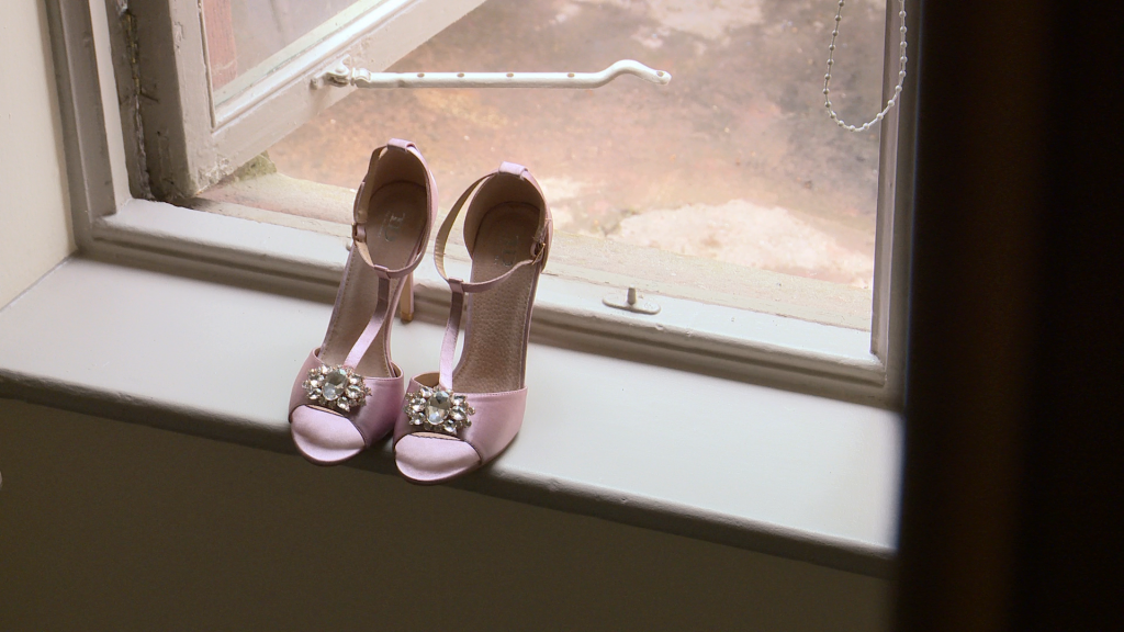 a strappy pink bridal sandal perches on a window sill at thornton manor in the wirral