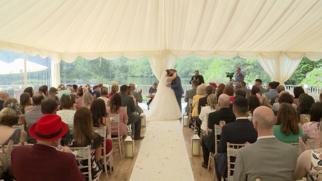 a wide shot of the ceremony as the bride and groom kiss