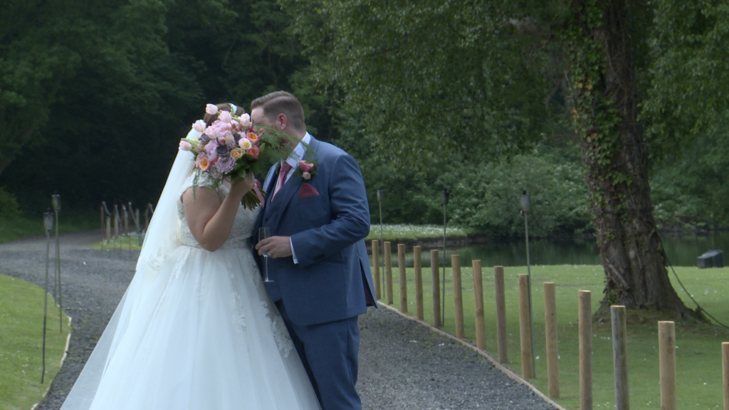 the bride and groom have a sneaky kiss behind her bouquet but the videographer films it