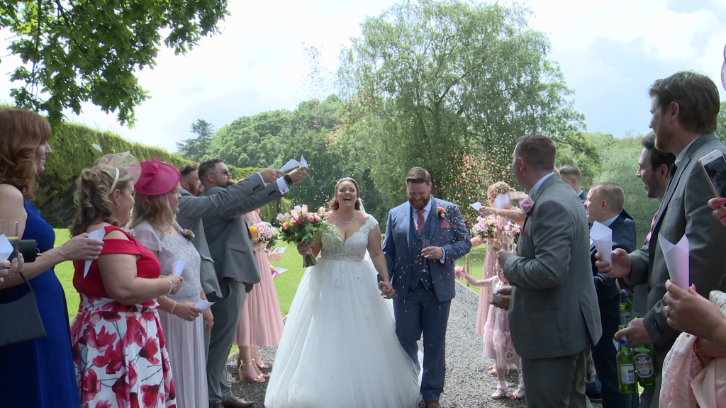 the bride laughs as she's showered in confetti holding her grooms hand alongside the lake at thornton manor