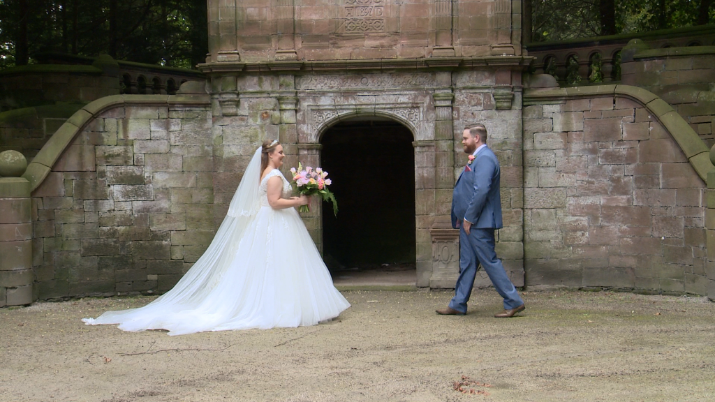 the bride and groom walk towards each other in front of a stone archway at thornton manor