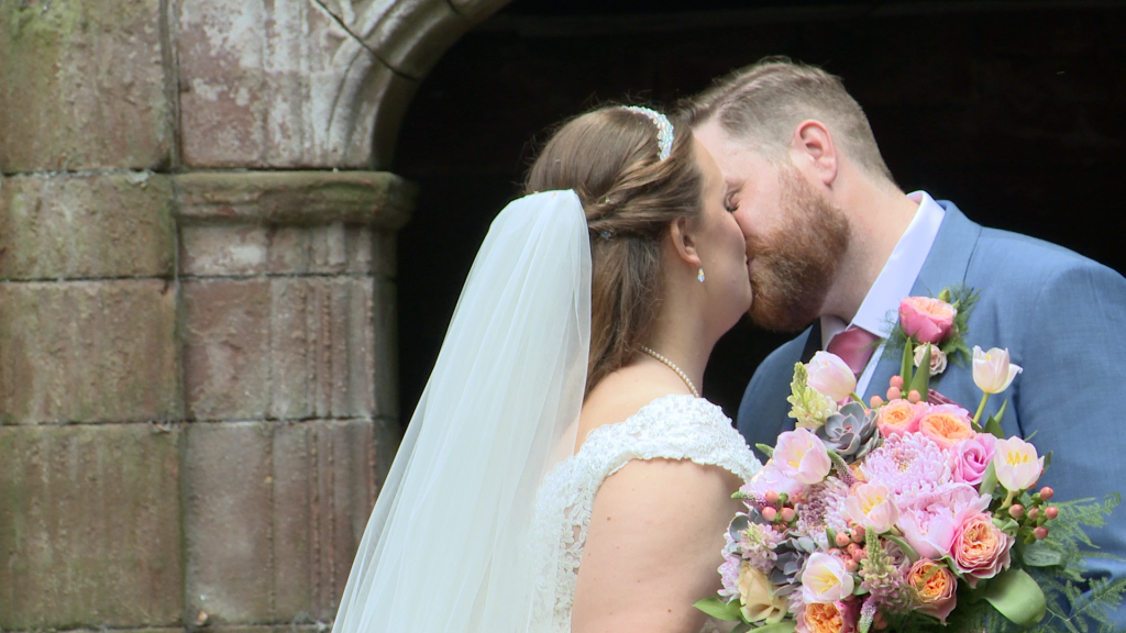 the bride and groom have a kiss for the wedding video and photographer