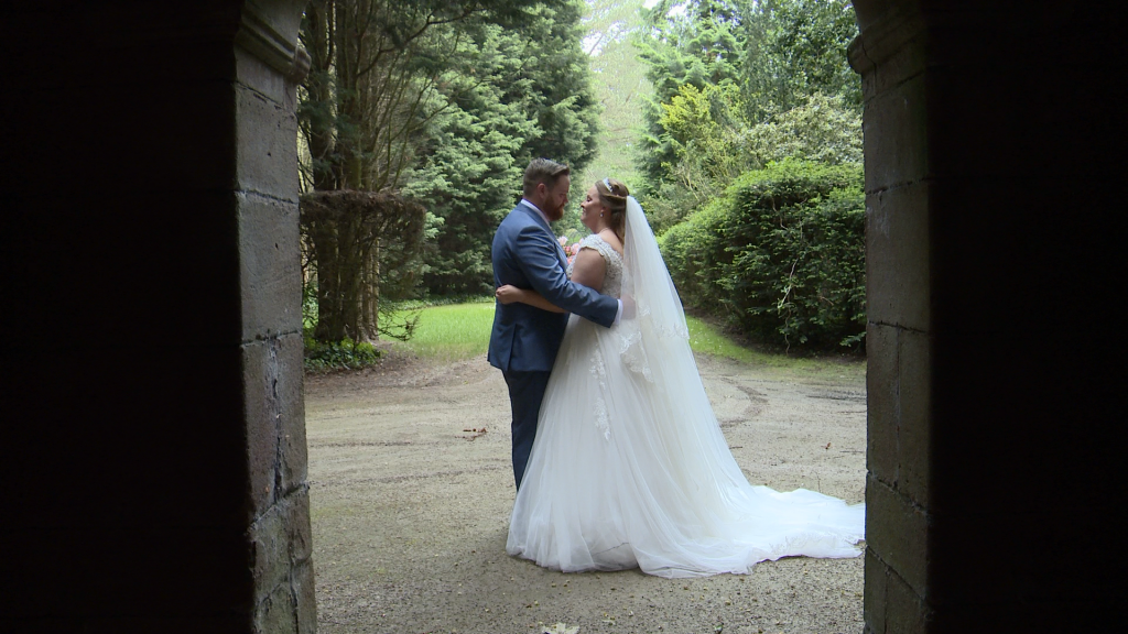 the bride and groom are framed in a stone archway at thornton manor in the wirral