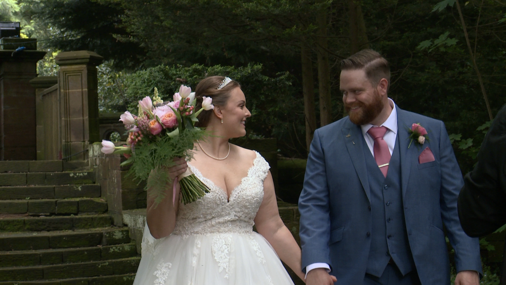 the bride and groom have a laugh and a chat as they walk towards their photographer Ioan at thornton manor