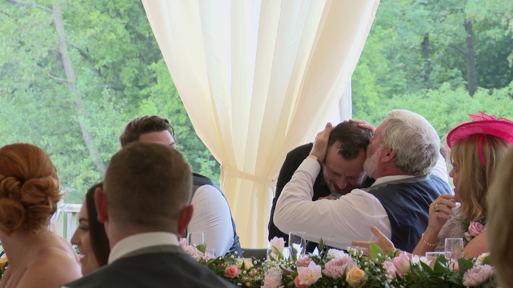silver service singers singing waiter gets a kiss on the head from the father of the groom during a surprise routine at thornton manor lakeside marquee
