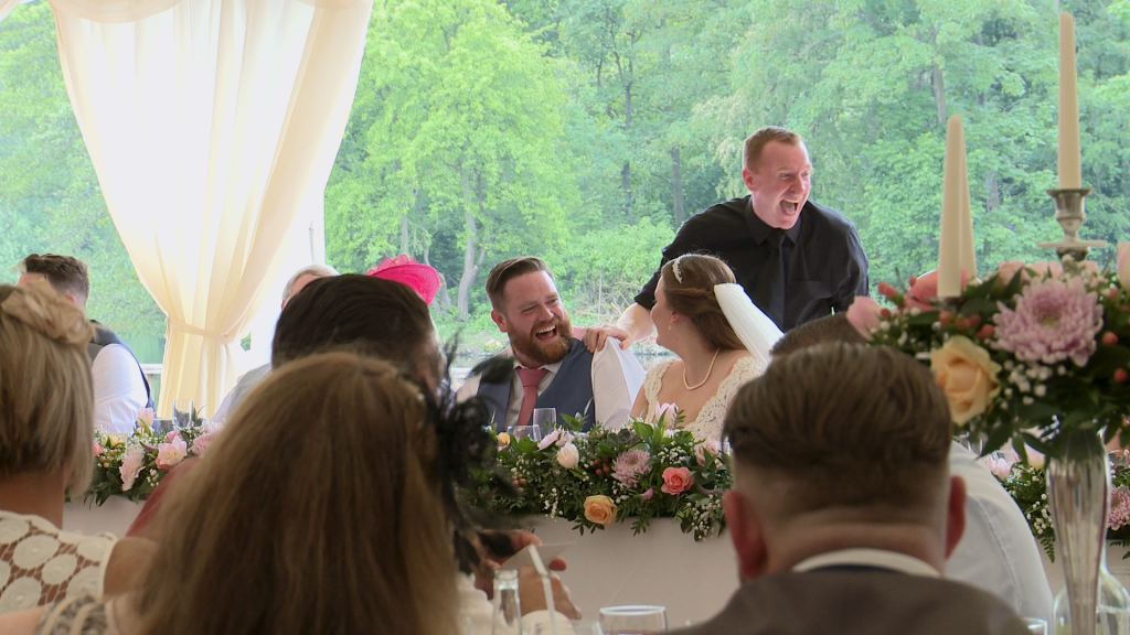 the groom has the singing waiter laughing during their set at the lakeside marquee