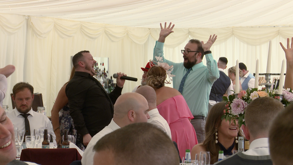 the silver service waiter has guests singing along during a wedding gig at the lakeside marquee at Thornton manor