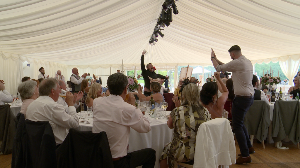 the singing waiter downs a pint much to the amusement of the wedding guests egging him on