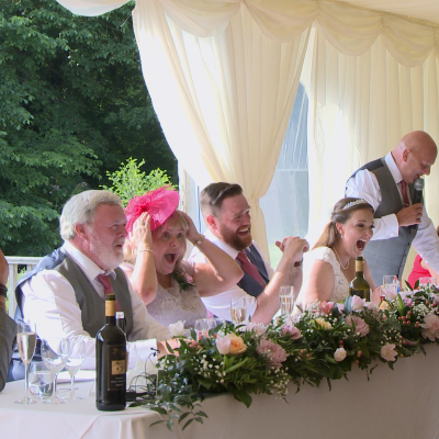 the brides dad says something funny about the bride and everyone is laughing and shocked he could be so funny