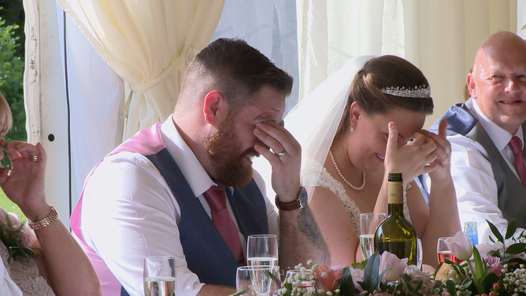 he groom and bride hide their faces in embarrassment during the best man speech