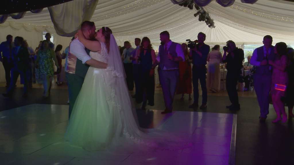 the bride and groom enjoy their first dance reveal at the lakeside marquee at thornton manor