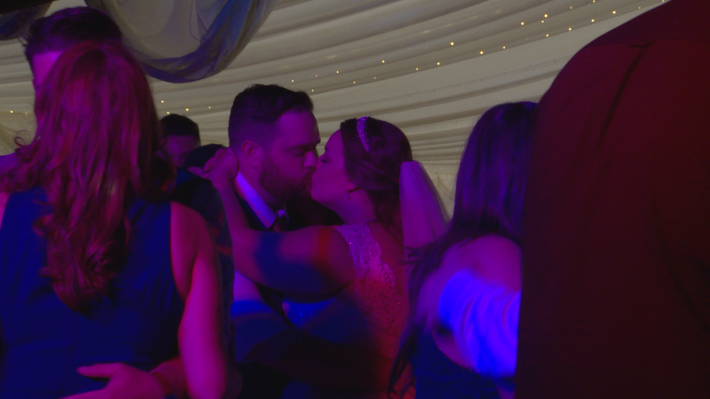 the bride and groom has a kiss on the dancefloor surrounded by their guests dancing at the lakeside marquee