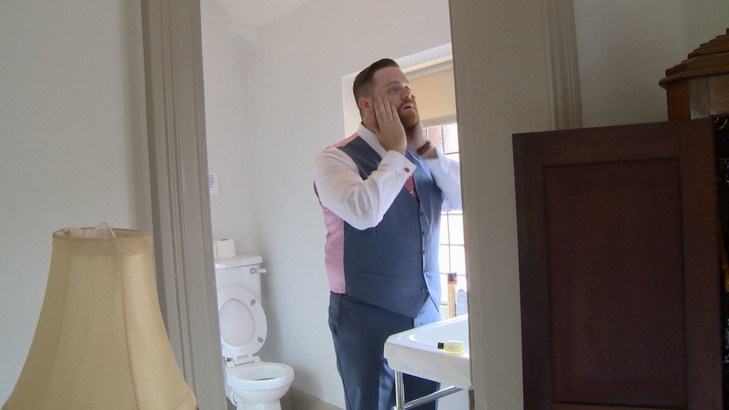 the groom gives his beard a smooth down in the bathroom at thornton manor