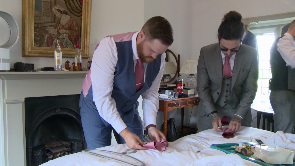 the groom and his usher work out how to fold their pocket squares