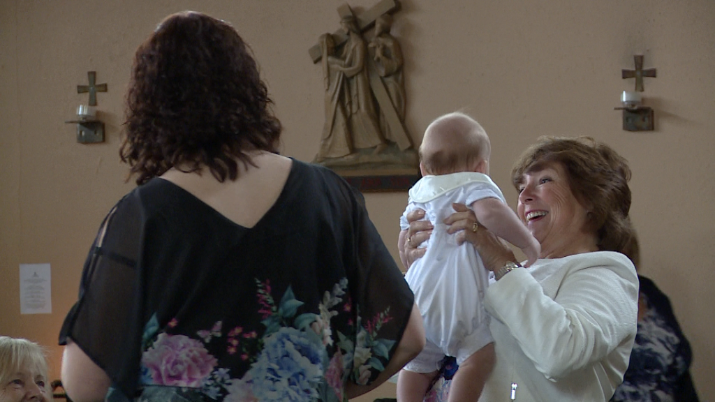 a grandma holds her grandson up high with a huge smile on her face before his christening in burtonwood