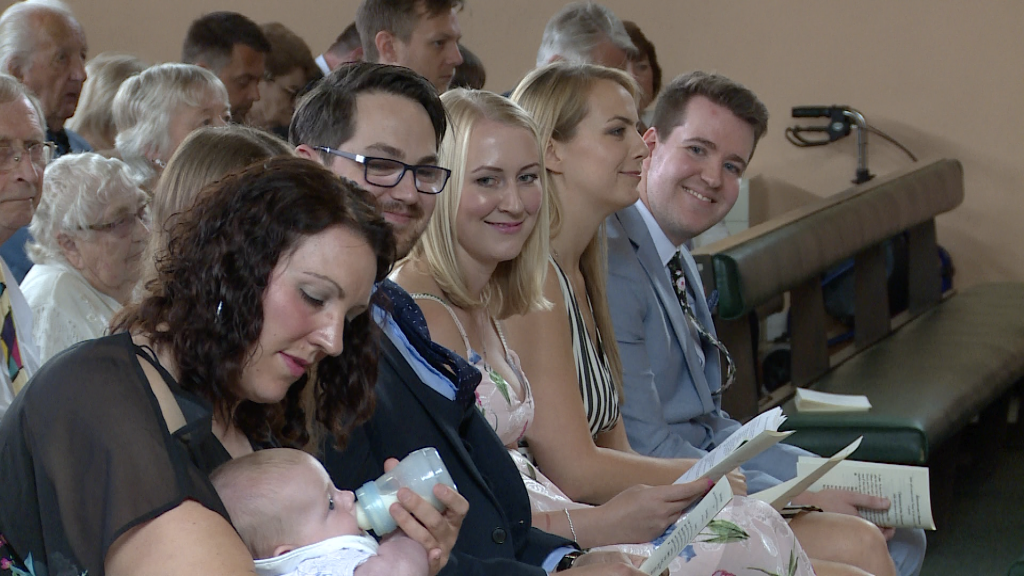 mum dad and godparents smile over at their baby boy having a bottle before his christening at st pauls in Burtonwood