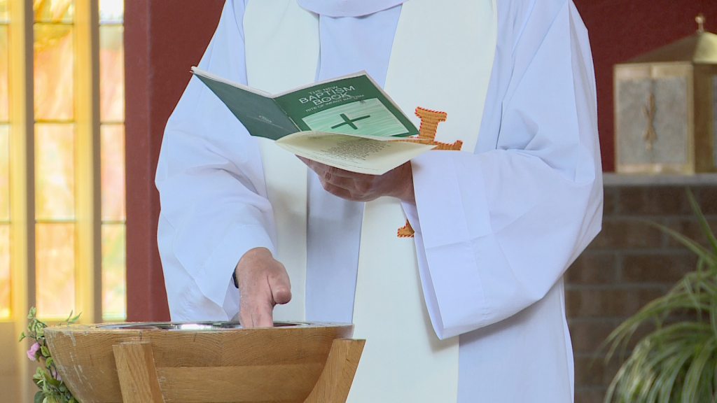 the priest dips his hand in the water as he reads his sermon before a chirstening at st pauls of the cross in Burtonwood