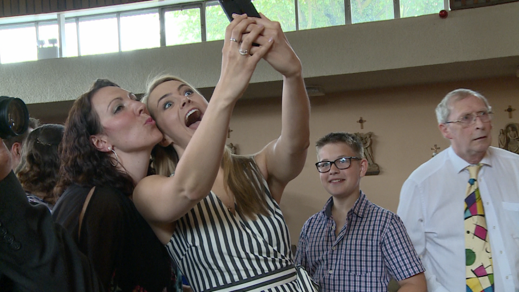 two friend pull silly faces at a phone in selfie mode during a christening at st pauls of the cross in Burtonwood