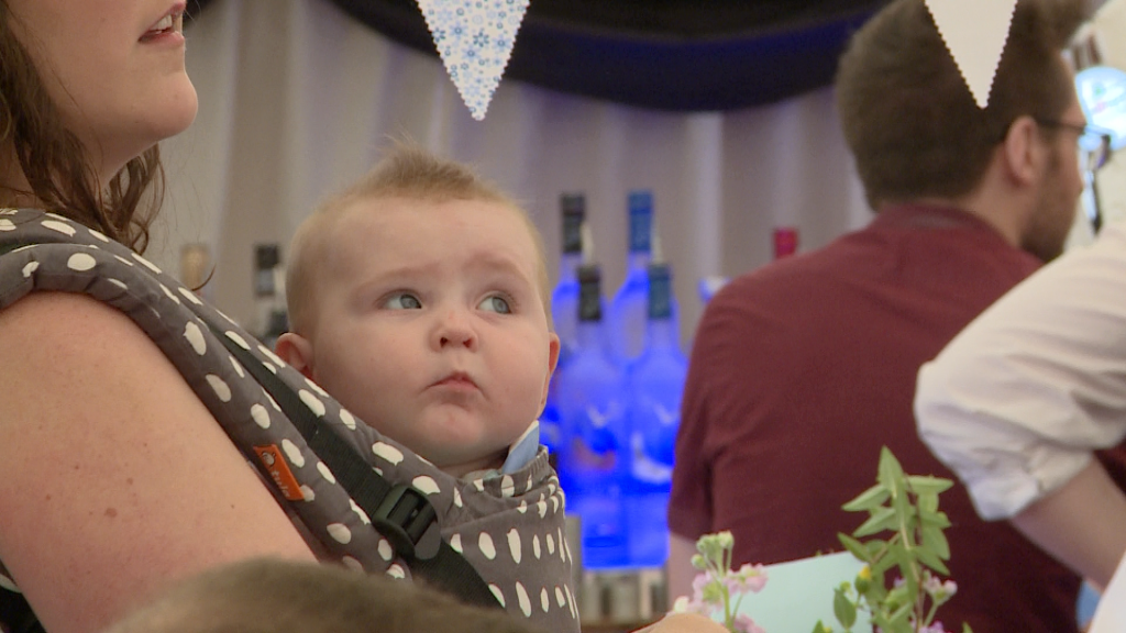 a cute baby girl looks up in a carrier on her mum at Alder Root Golf Club marquee for a christening party