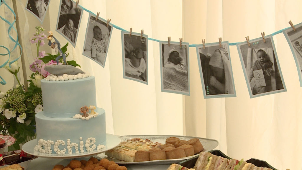 a blue homemade christening cake lion king theme sits on the buffet table with milestone baby boy bunting