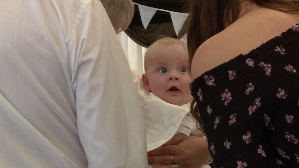 a baby looks wide eyed at a guest pulling faces at them at a christeing party at Alder Root Golf Club in Warrington