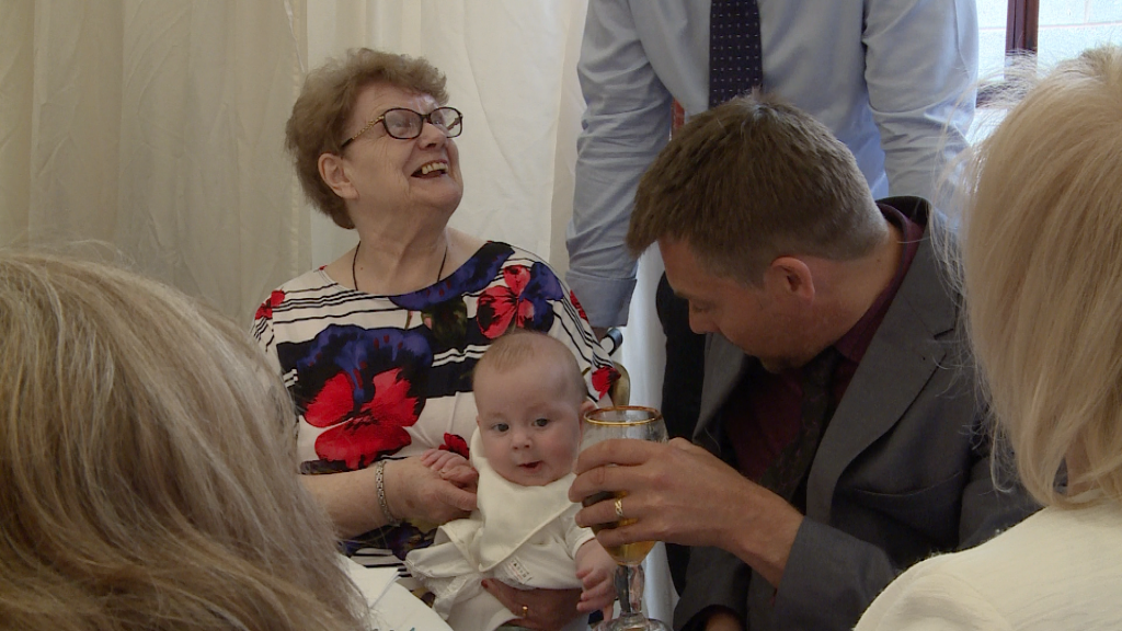 family enjoy having a cuddle with the christening boy and someone jokingly holds a pint near him in Warrington