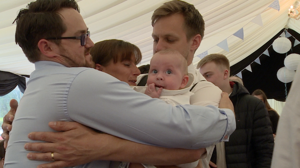 a video captures a big family hug with a baby boy Archie in the middle looking confused at his christening party