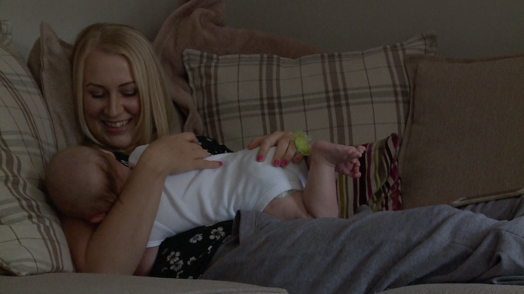 a mum enjoys a sleepy cuddle on her sofa at her home in Appleton before his christening