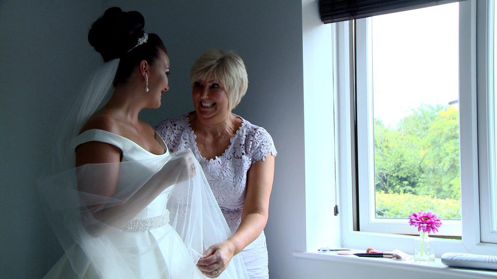 the mother of the bride shrugs her shoulds in excitement as she helps her daughter with the finishing touches to her wedding outfit with the videographer and photographer capturing the moment in their home in the wirral